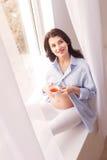 La femme enceinte gaie boit la boisson chaude Images libres de droits