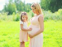 La femme enceinte heureuse, fille de petit enfant touche la mère de ventre Images libres de droits
