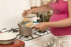 La femme enceinte livre la nourriture bourrée Photo stock