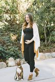 La femme enceinte marche avec son petit animal familier Boston Terrier dehors et est heureuse image libre de droits