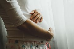 La femme enceinte mignonne dans des pyjamas rep?r?s frotte son ventre pr?s de la fen?tre Photo tendre et ?treinte heureuse de gro photographie stock