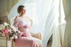 La femme enceinte mignonne s'asseyant sur les rideaux se soulevants proches en chaise et les étreintes se gonflent avec amour Photos stock
