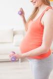 La femme enceinte mignonne s'exerce avec des poids photographie stock