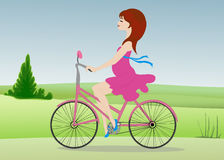 La femme enceinte monte une bicyclette à travers le champ Image libre de droits