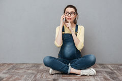 La femme enceinte parlant par le téléphone portable et font le geste de silence Photo libre de droits