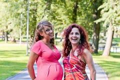 La femme enceinte parle à l'amie Photos stock