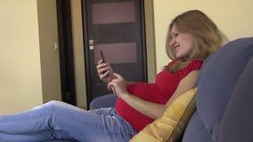 La femme enceinte passent en revue les photos et l'Internet avec le smartphone banque de vidéos