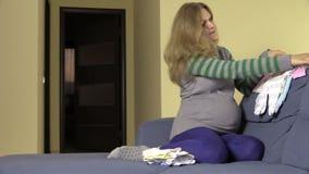 La femme enceinte préparent les corps et les plantes grimpantes nouveau-nés sur le sofa banque de vidéos