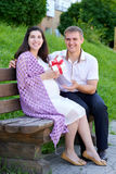 La femme enceinte prend un cadeau de son mari, famille heureuse, couples en parc de ville, saison d'été, herbe verte et arbres Photographie stock
