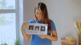 La femme enceinte regardant sa première échographie de bébés résulte banque de vidéos