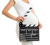 La femme enceinte remet tenir le panneau de clapet sur son ventre photographie stock libre de droits