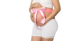La femme enceinte remet tenir le ventre avec le cadeau de ruban bleu sur la cloche Images libres de droits