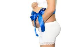 La femme enceinte remet tenir le ventre avec le cadeau de ruban bleu sur la cloche Photographie stock libre de droits