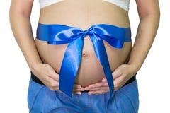 La femme enceinte remet tenir le ventre avec le cadeau de ruban bleu sur la cloche Photos stock