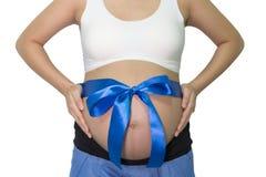 La femme enceinte remet tenir le ventre avec le cadeau de ruban bleu sur la cloche Image libre de droits