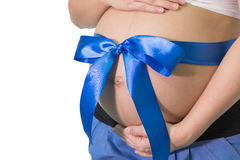 La femme enceinte remet tenir le ventre avec le cadeau de ruban bleu sur la cloche Photos libres de droits