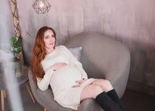 La femme enceinte rousse s'assied dans une chaise photo stock