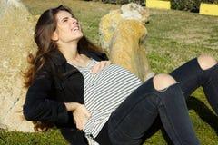 La femme enceinte s'asseyant dans des contractions de sentiment de parc a effrayé la douleur de sentiment Images libres de droits