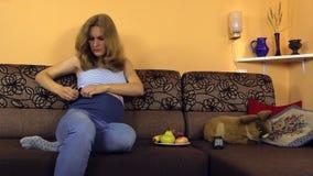 La femme enceinte s'asseyent sur le divan et règlent la courroie spéciale de pantalons clips vidéos