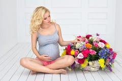 La femme enceinte s'assied près des fleurs Photographie stock libre de droits