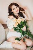 La femme enceinte s'est habillée dans une tunique blanche et des chaussures blanches, tenant un bouquet des roses photographie stock