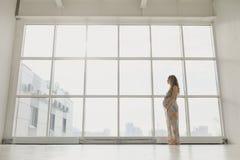 La femme enceinte se tient prêt la fenêtre Photographie stock libre de droits