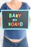 La femme enceinte stocke un texte coloré de bébé à bord sur le tableau noir au-dessus de son ventre Photographie stock