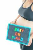 La femme enceinte stocke un texte coloré de bébé à bord sur le tableau noir au-dessus de son ventre Photo libre de droits