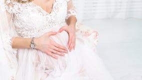 La femme enceinte tenant ses mains sous forme de coeur sur elle soit Image stock