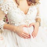 La femme enceinte tenant ses mains sous forme de coeur sur elle soit Photo stock