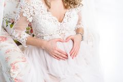La femme enceinte tenant ses mains sous forme de coeur sur elle soit Images libres de droits