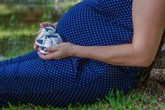 La femme enceinte tient ses chaussures du ` s de fils images stock