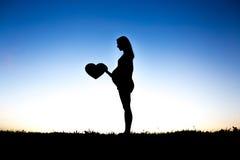La femme enceinte touchent son ventre se reposent au sol contre la lumière photographie stock libre de droits