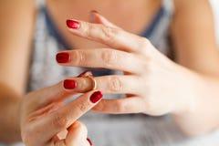 La femme enlève l'anneau de la main Photographie stock libre de droits
