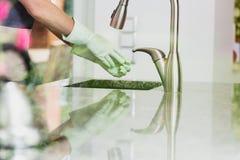La femme enlève les gants en caoutchouc verts photographie stock libre de droits