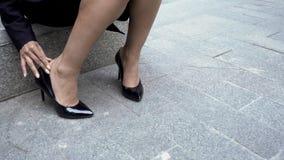 La femme enlevant les chaussures serrées de talon haut, douloureuses frôlent sur des pieds, veines variqueuses photos libres de droits