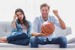 La femme a ennuyé par son match de basket de observation d'associé Photo stock