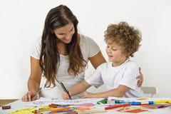 La femme enseigne à son enfant comment dessiner Photo stock