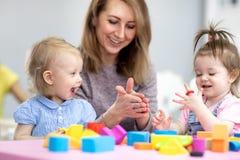 La femme enseigne des enfants modelant la pâte à modeler au centre de soins de jour photographie stock