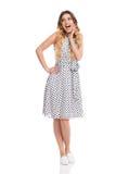 La femme enthousiaste dans la robe pointillée par blanc est criante et regardante loin Images stock