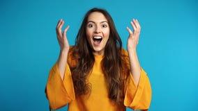 La femme enthousiaste et étonnée heureuse apprécient de bonnes nouvelles sur le fond bleu banque de vidéos
