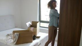 La femme entrant dans le nouveau déballage à la maison vêtx de la chambre à coucher banque de vidéos