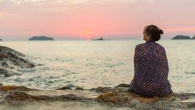 La femme enveloppée dans le plaid repose seul sur le voyage de côte photographie stock libre de droits