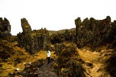La femme erre par des formations de lave en Islande photographie stock libre de droits