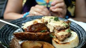 La femme essuie la table avec la serviette avant de manger des pommes de terre de rôti avec de la sauce banque de vidéos