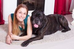 La femme est à la maison à côté de la cheminée avec son grand chien Cane Corso Photos stock