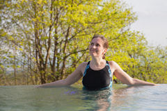 La femme est des repos dans la piscine extérieure Photographie stock libre de droits