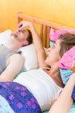La femme est fâchée et tient le nez de son associé de ronflement Images stock