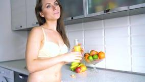 La femme est habillée en jus d'orange de boissons de lingerie sur la cuisine clips vidéos