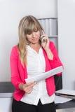 La femme est téléphonante et regardante un calendrier Photos libres de droits